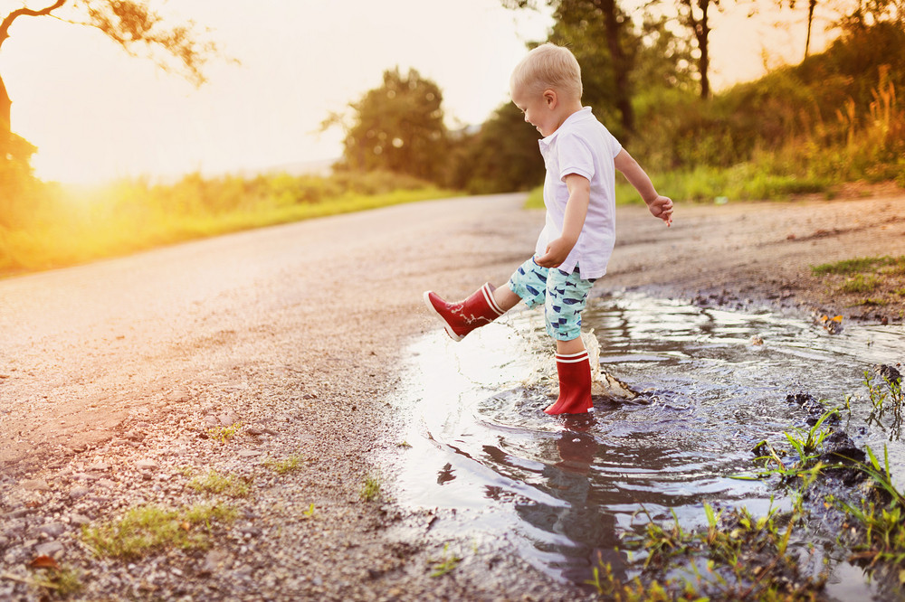 Little boy playing outside in a puddle