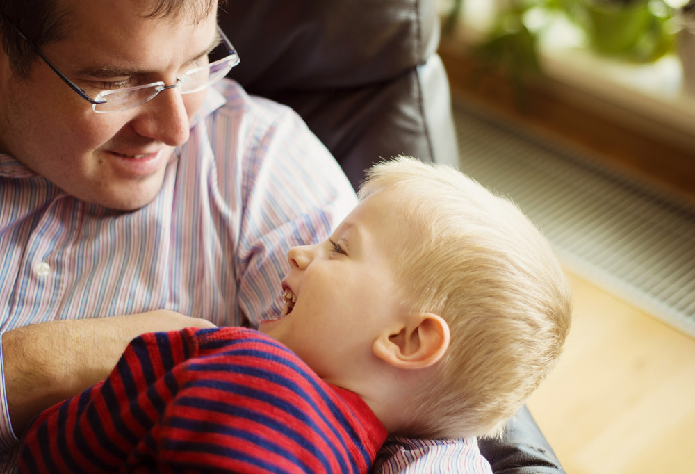 Little boy relaxing at home with his father