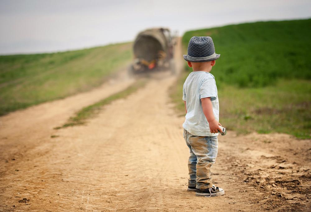 Little boy walking on the footpath in field