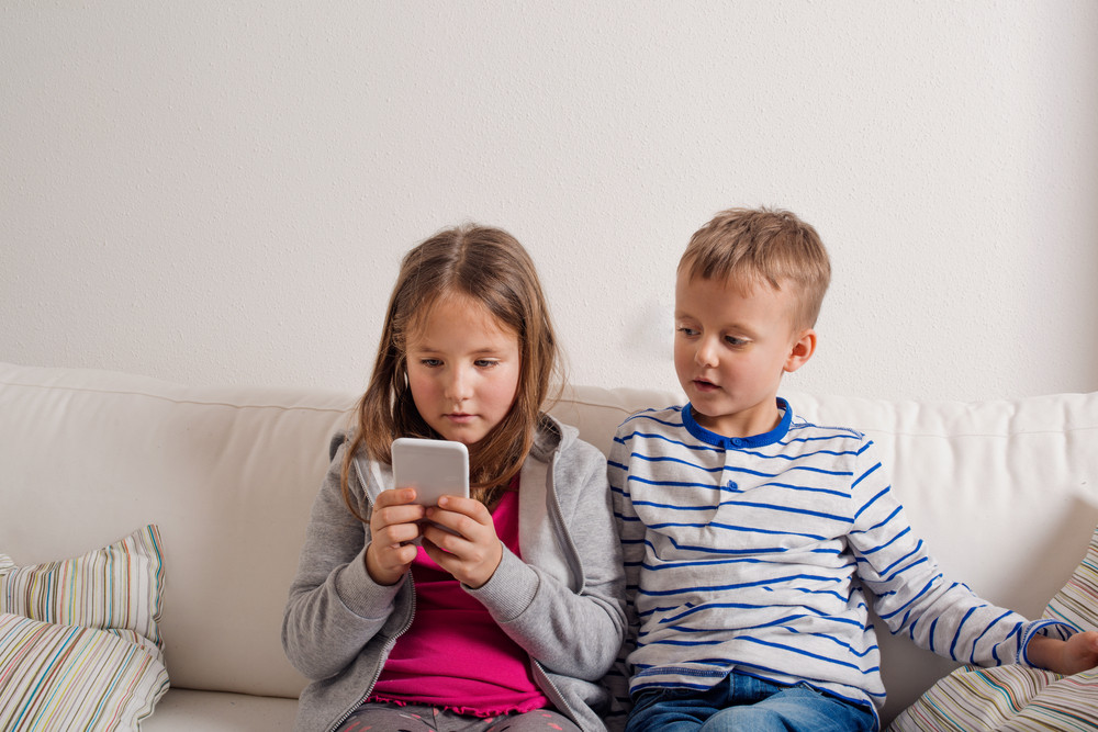 Little girl and boy sitting on sofa with a smart phone at home. Happy children playing indoors, copy space