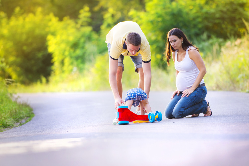 Little girl fallen of her bike, her parents helping her to stand up