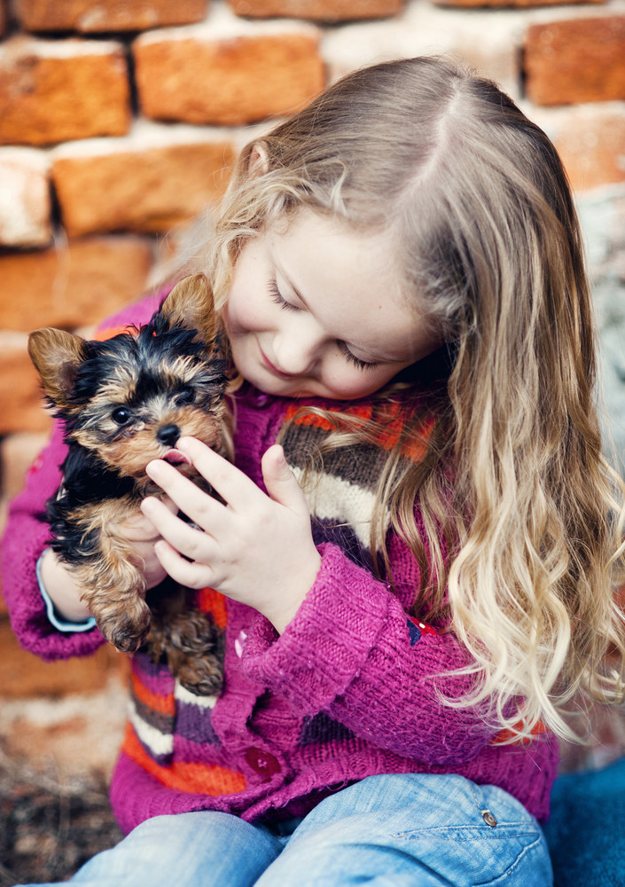 Little girl is playing with her puppy by brick wall