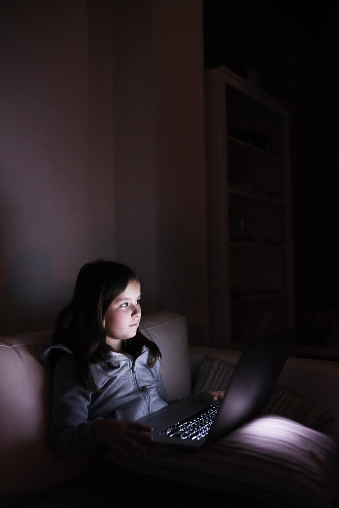 Little girl, sitting in a dark, playing with laptop. Child at home, sitting on sofa.