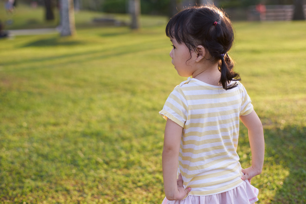 little girl standing turned her back on wide green meadow
