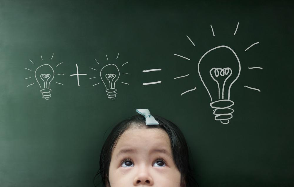 Little girl with light bulb on the blackboard background.