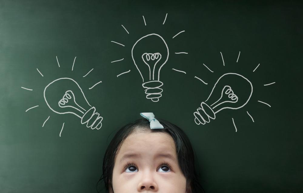 黒板背景に電球を持つ少女。