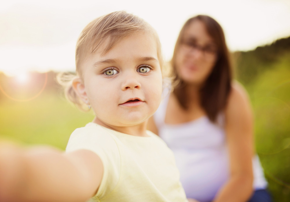 Little girl with mum in background taking selfie by mobile phone
