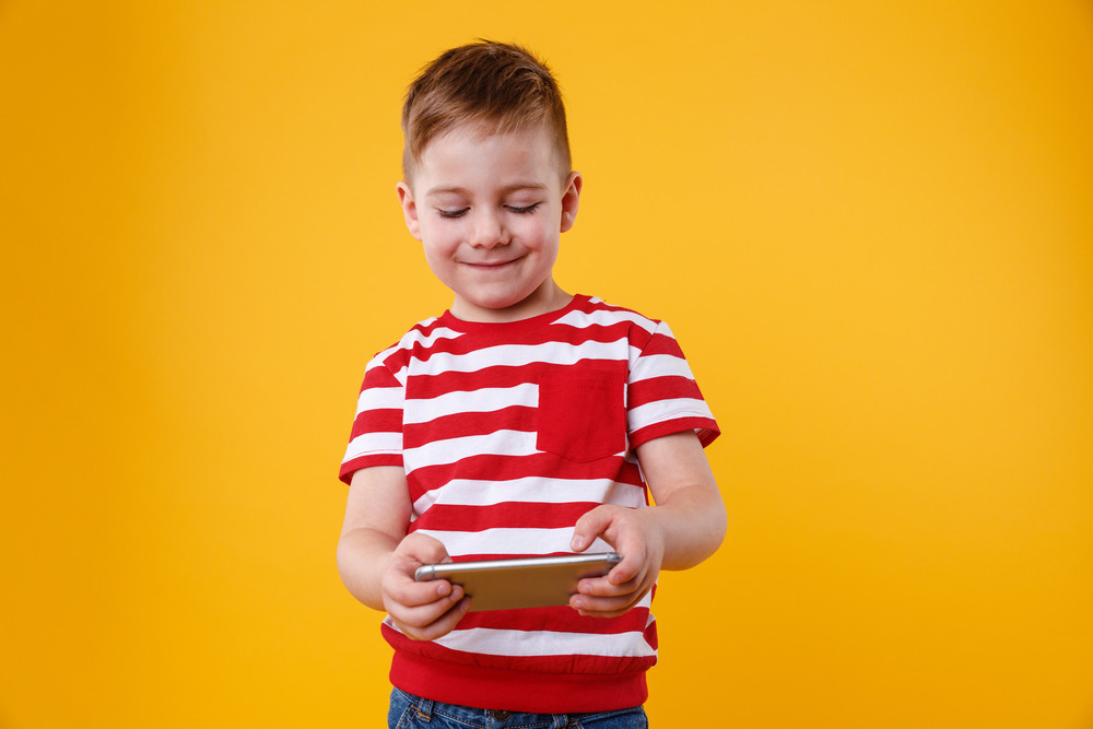 Little smiling child boy playing games or surfing internet on digital smartphone isolated over orange background