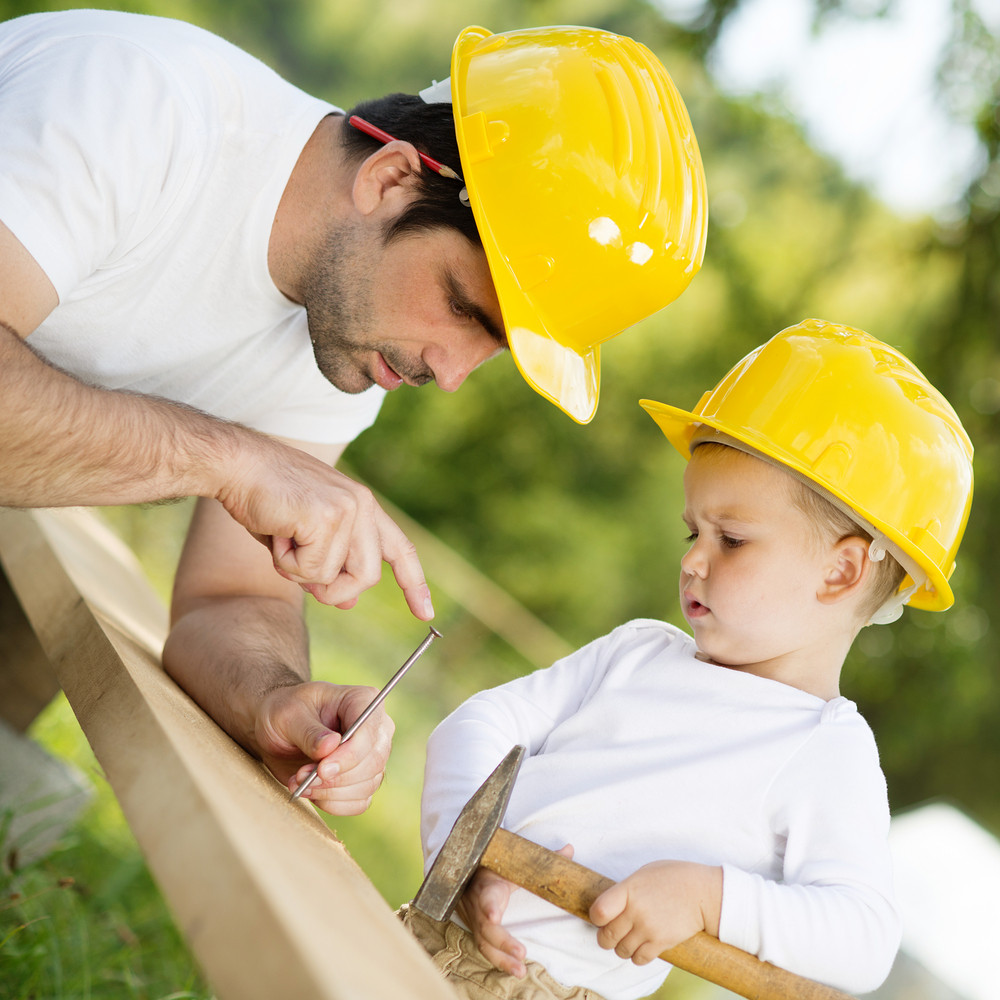 Little son helping his father with building work