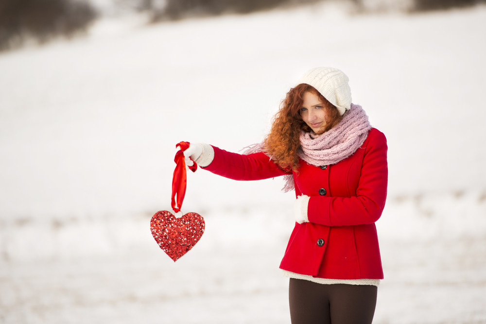 Lonely girl in the red coat is holding a red heart and waiting.