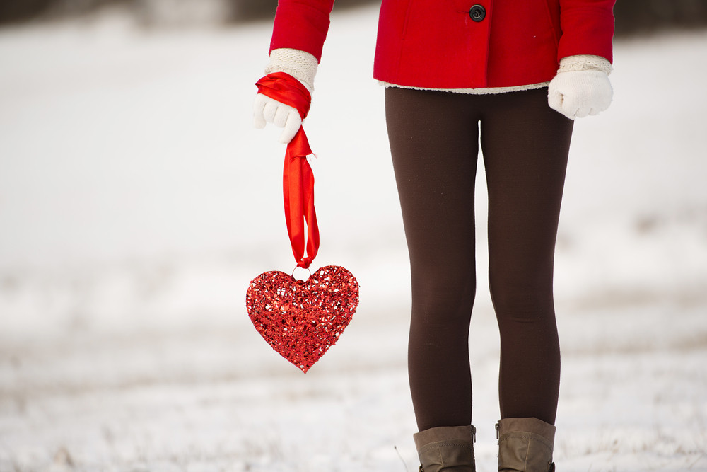 Lonely girl in the red coat is holding heart and waiting.