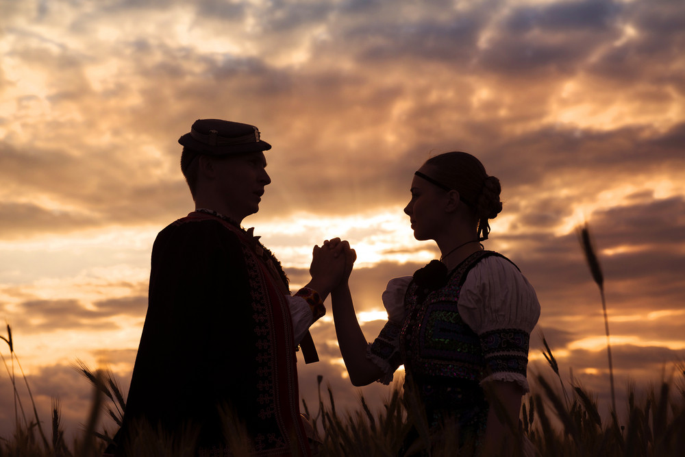 Love couple in sunset field. They wearing traditional Eastern Europe folk costumes.