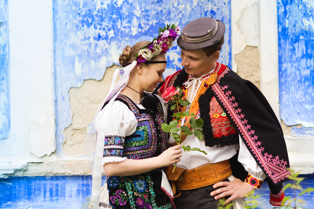 Love couple standing by the blue wall wearing traditional Eastern Europe folk costumes.