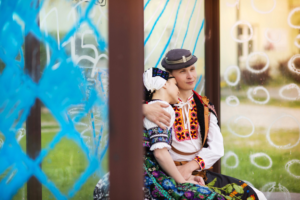 Love couple wearing traditional Eastern Europe folk costumes sitting at the bus stop.