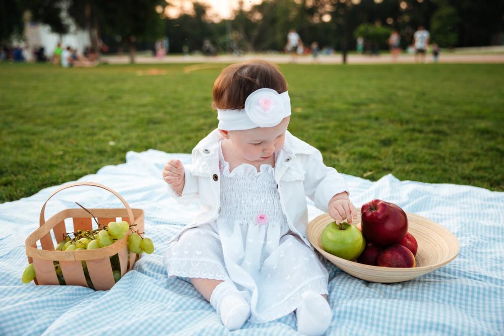 Lovely little girl sitting and choosing apple on picnic in park