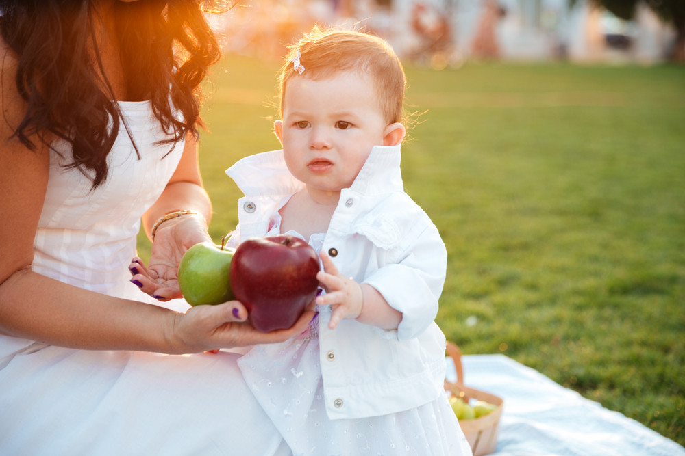Lovely little kid taking apples from her mom outdoors