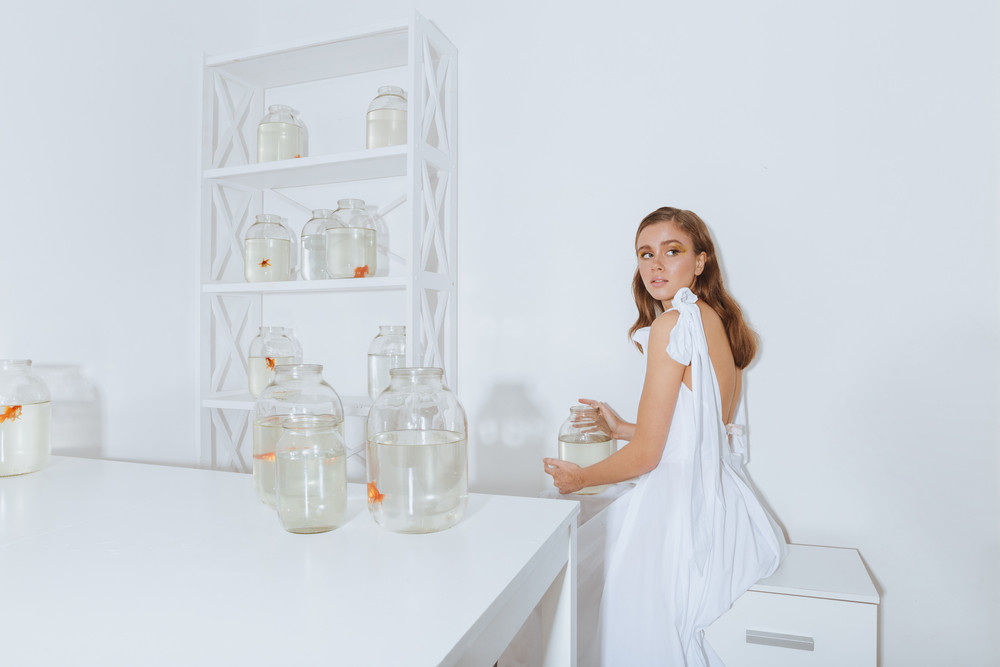 Lovely young woman in dress holding jar with gold fish in the room