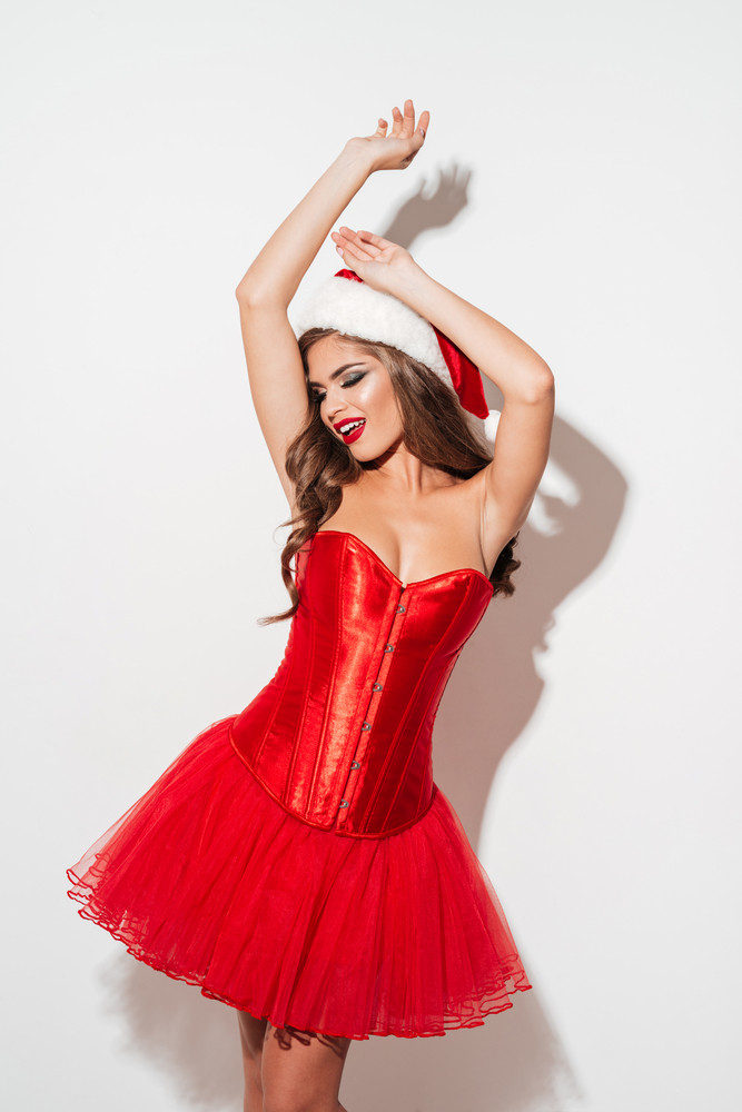Lovely young woman in red santa claus outfit posing with raised hands isolated on the white background