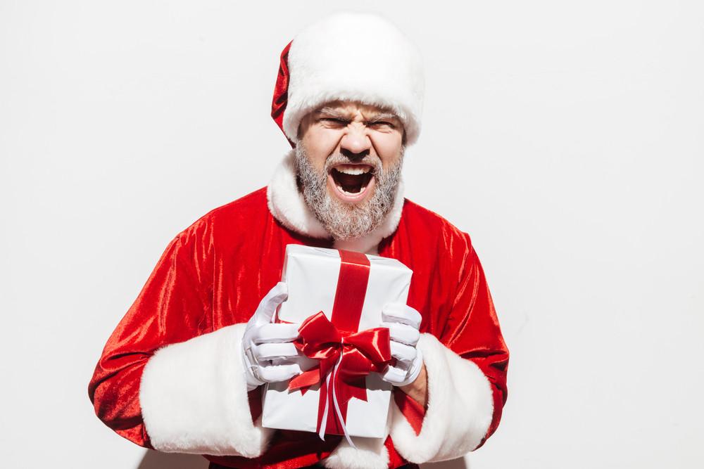Mad irritated man santa claus holding present box and shouting