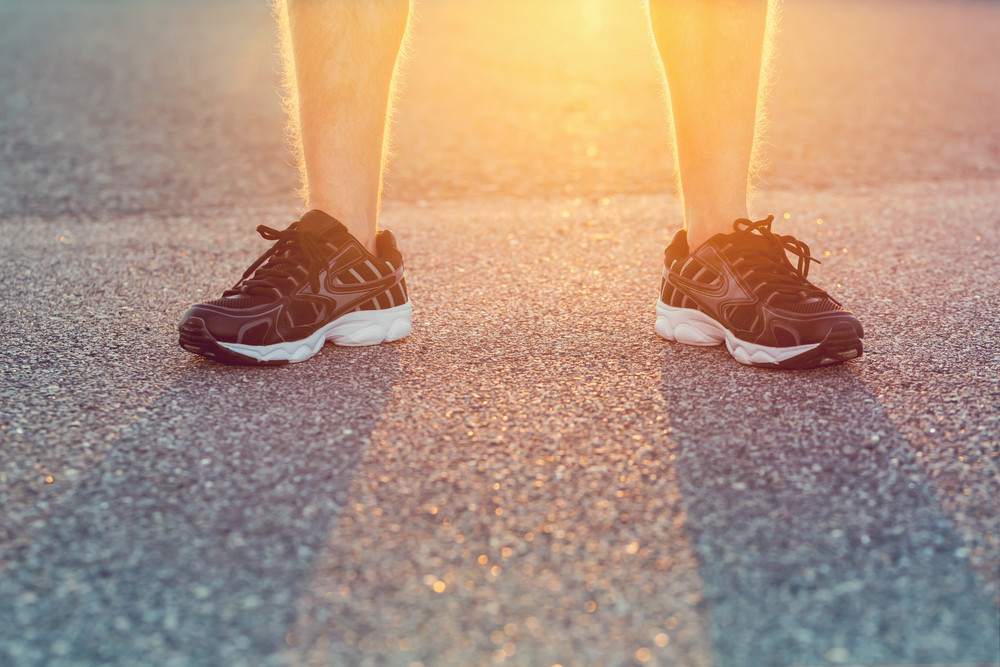 Male athlete in running shoes ready for a run at sunset