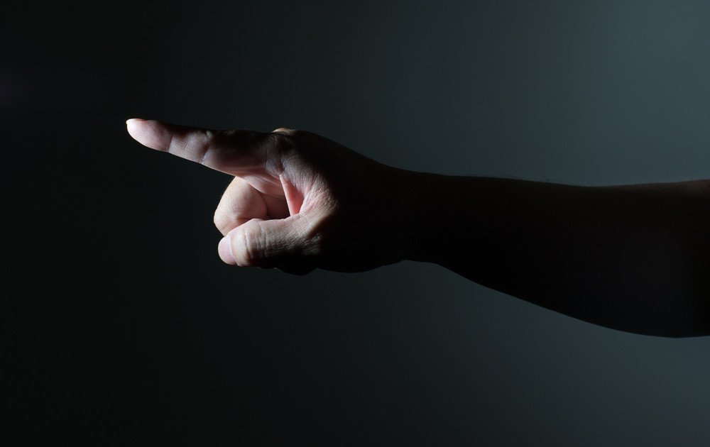 Male hand with finger pointing on dark background