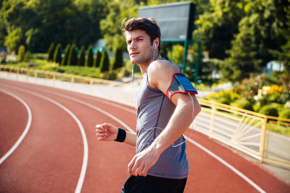 Male runner listening to music with mobile phone at the stadium and looking at camera