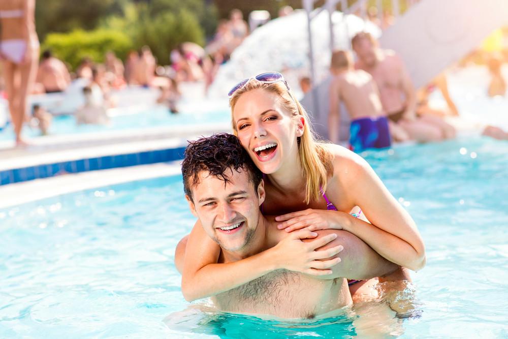 Man and woman in bikini on piggyback in the swimming pool, with baloon. Summer heat, sun and water.
