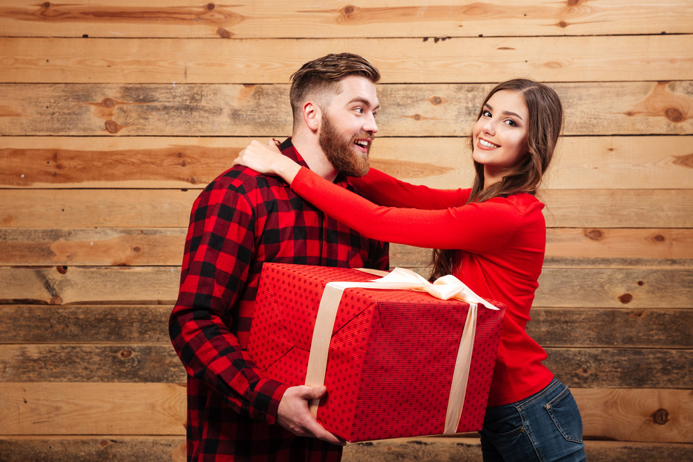 Man and woman with gift. wooden background