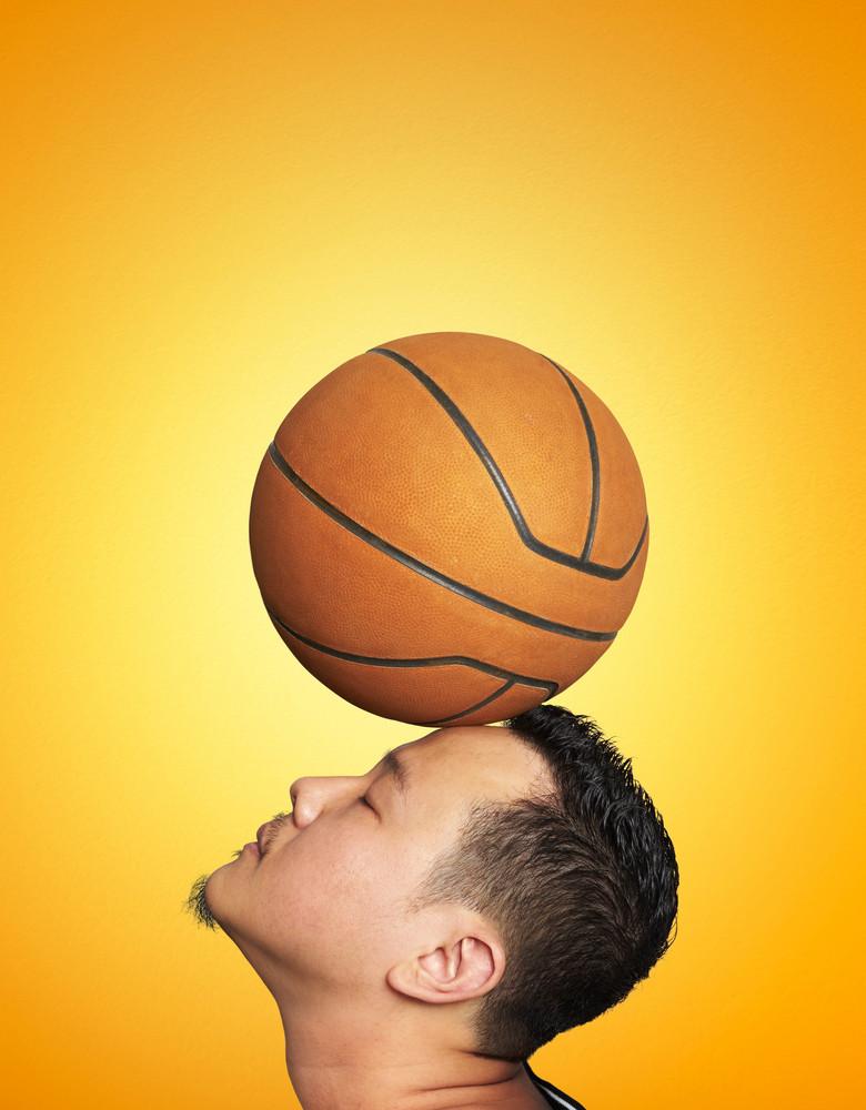 Man balancing basketball on his head ,Orange wall background .