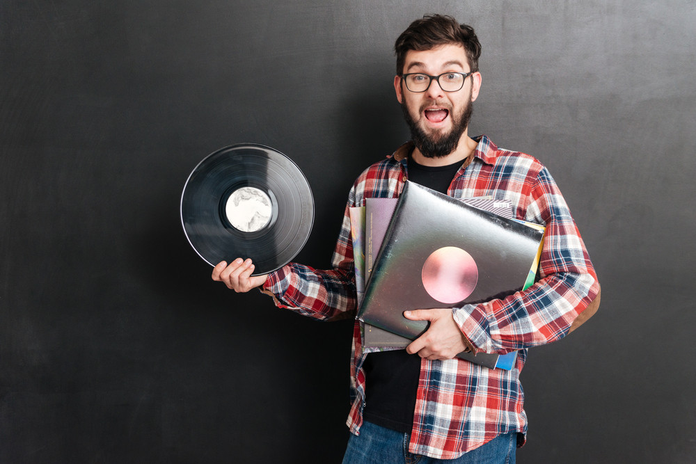 Man dressed in shirt in a cage standing over chalkboard while holding vinyl records in hands