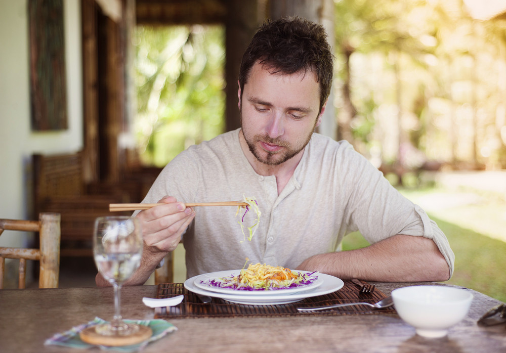 Man enjoying a meal with chopsticks in vietnamese restaurant