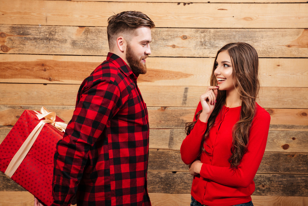 Man gives woman big gift. wooden background