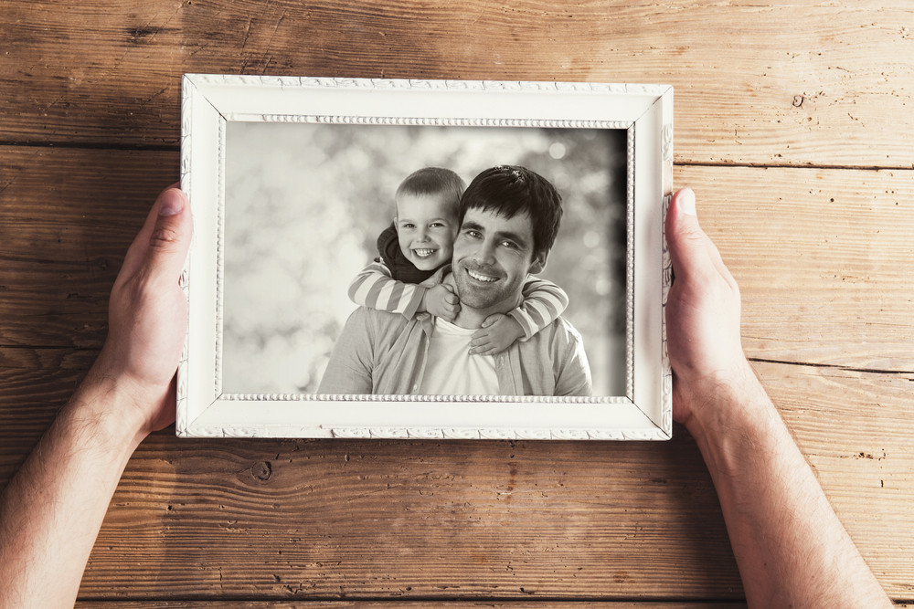 Man holding a picture frame with family photo on a wooden background.