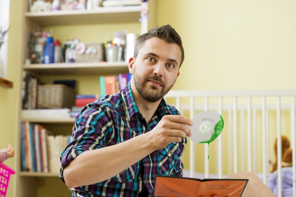 Man holding damaged CD sitting on florr in bedroom
