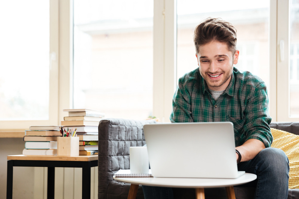 Man in green shirt sitting on sofa at the table and looking at laptop in office. Coworking