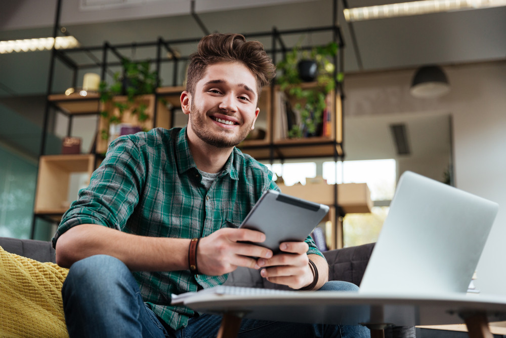 Man in green shirt sitting on sofa by the table with tablet and laptop in office. Coworking