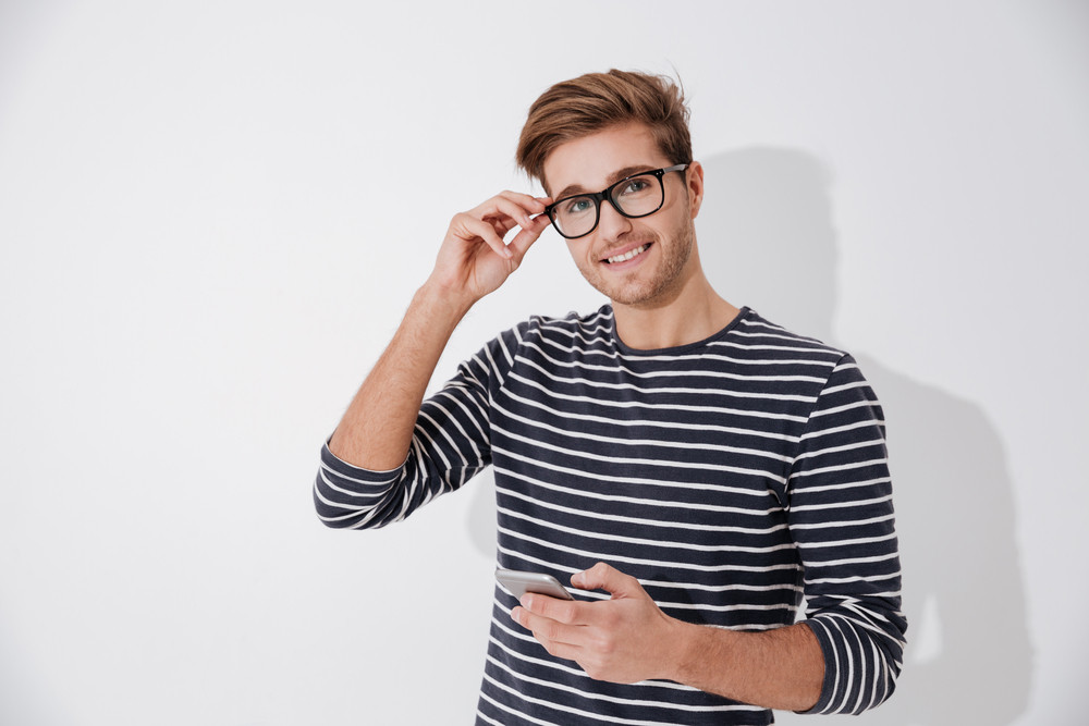 Man in striped sweater and eyeglasses holding phone and looking at camera. Isolated gray background