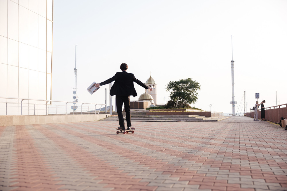 Man in suit on skate. so happy. with newspaper