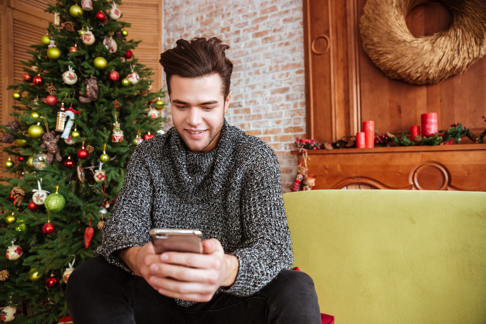 Man in sweater sitting on sofa with phone near the fir-tree