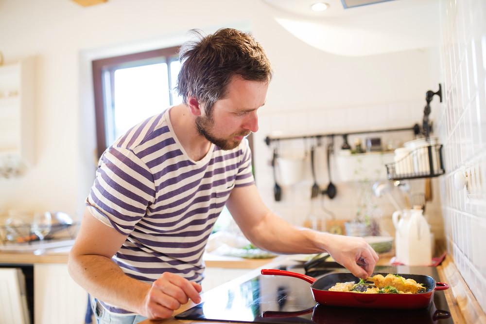 Man in the kitchen preparing king prawns