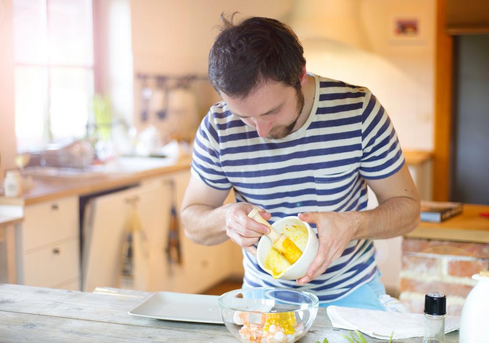 Man in the kitchen preparing prawns for a dinner