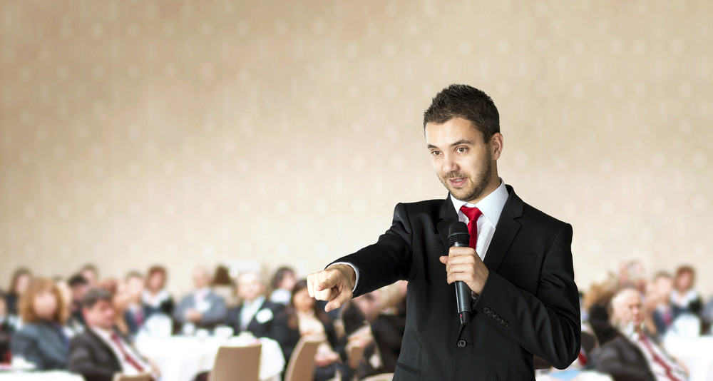 Man is speaking on indoor business conference for managers.