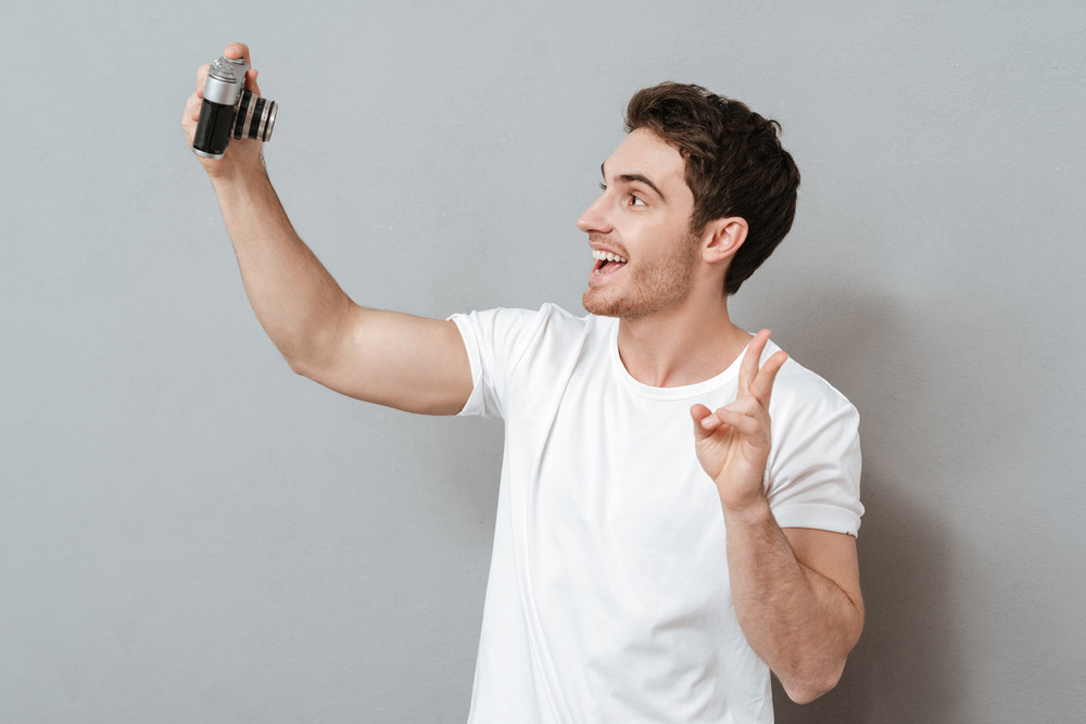 Man making selfie on retro camera in studio. Isolated gray background