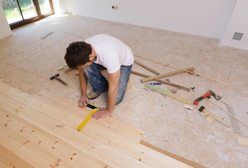 Man measuring wood flooring in new house