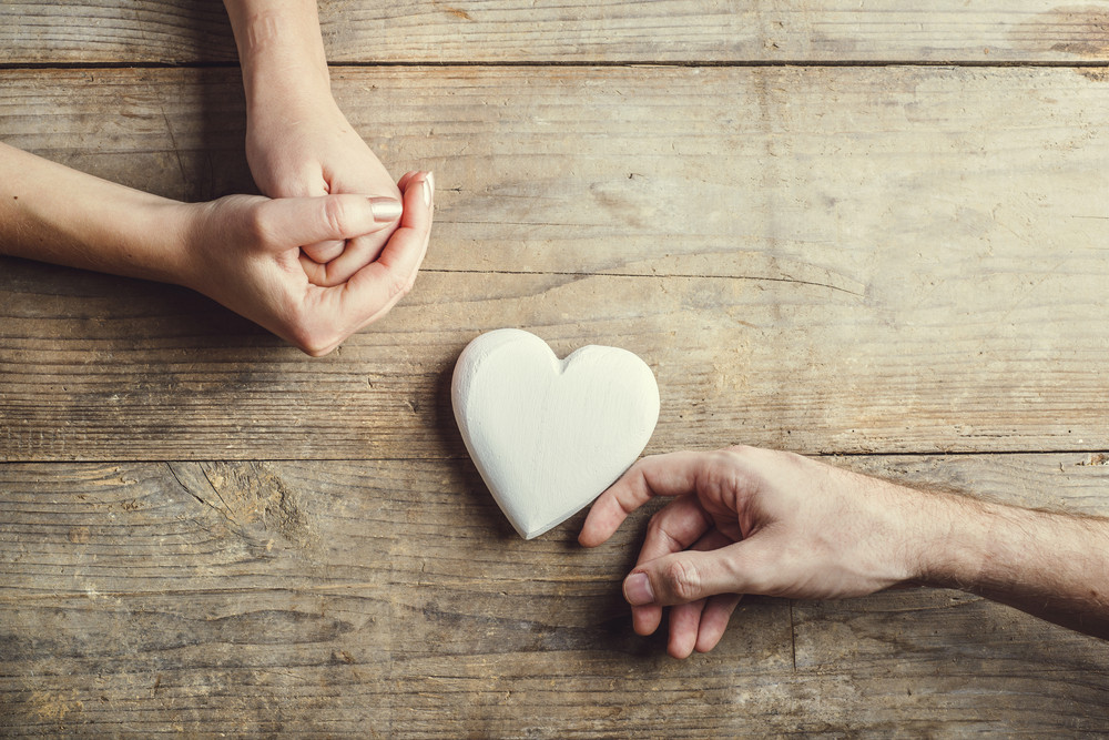 Man offering a white heart tenderly to a woman. Studio shot on a wooden background, view from above.