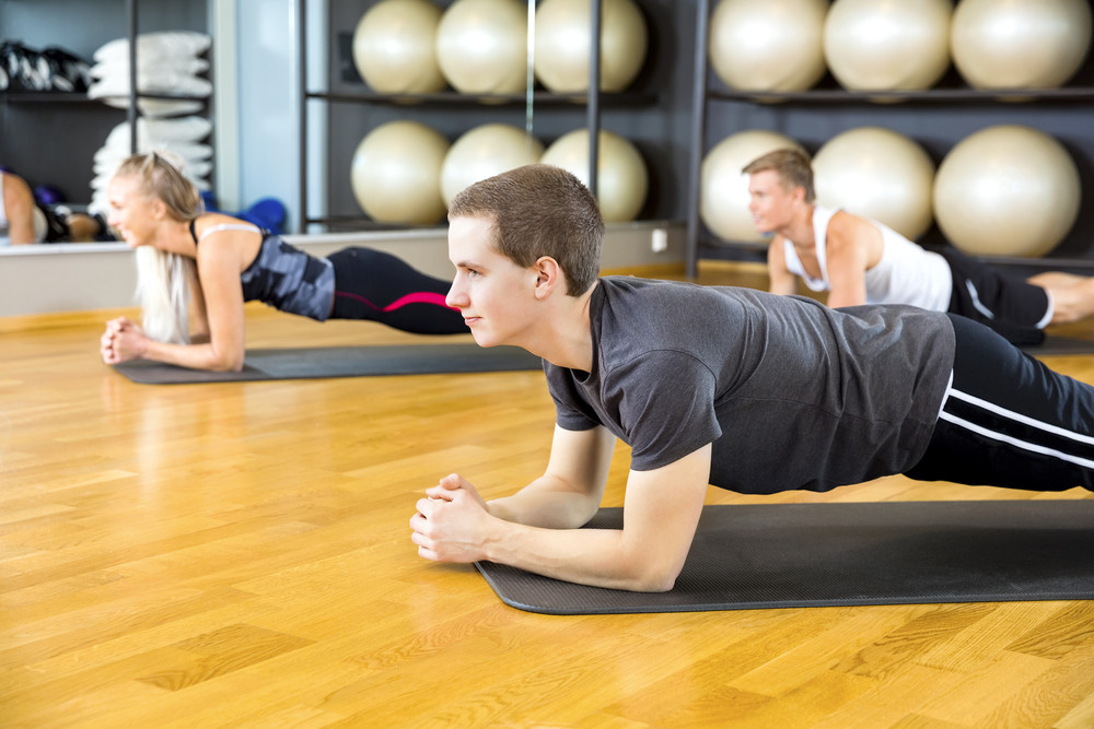 Man Performing Plank Exercise With Friends