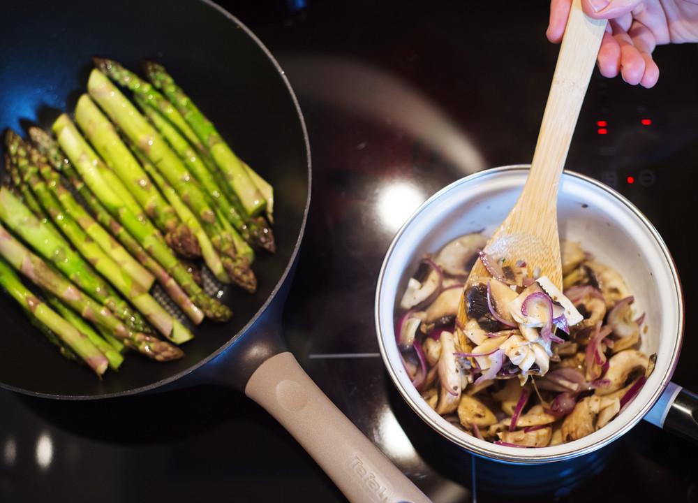 Man preparing creamy mushroom sauce and green asparagus