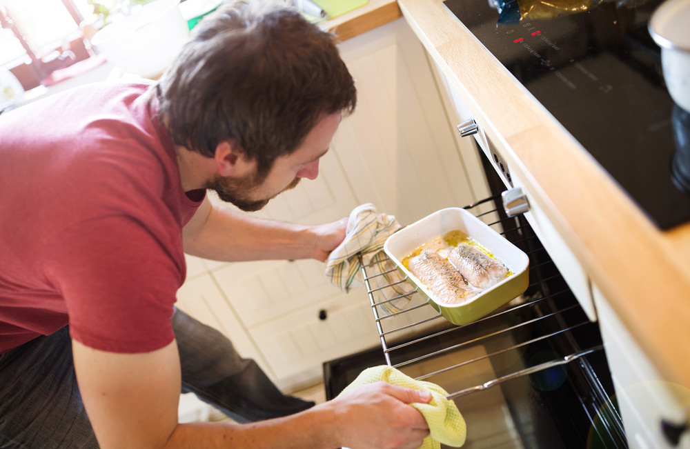 Man preparing grilled salmon in the oven