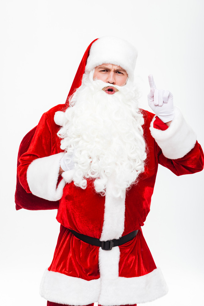 Man santa claus with gift sack talking and pointing up