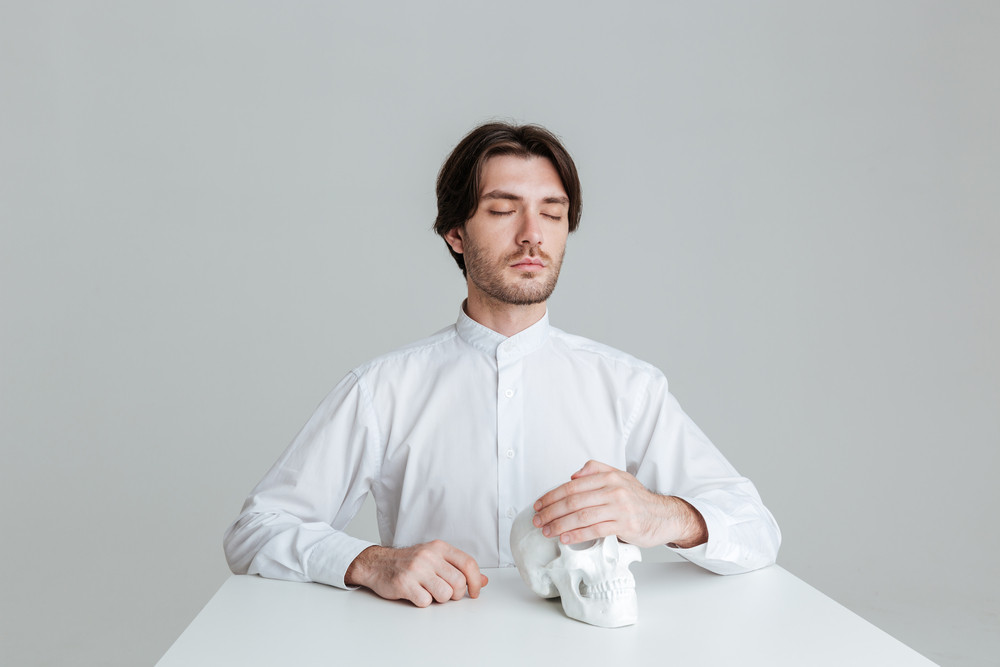 Man sitting with eyes closed holding fake skull at the table isolated on the gray background